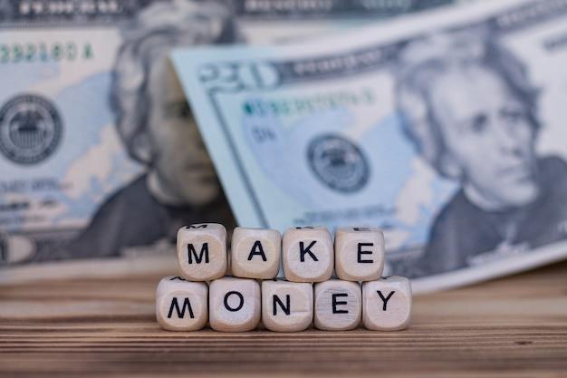 Słowa make money, wyłożone literami na drewnianych kostkach na tle banknotów dolarowych.
