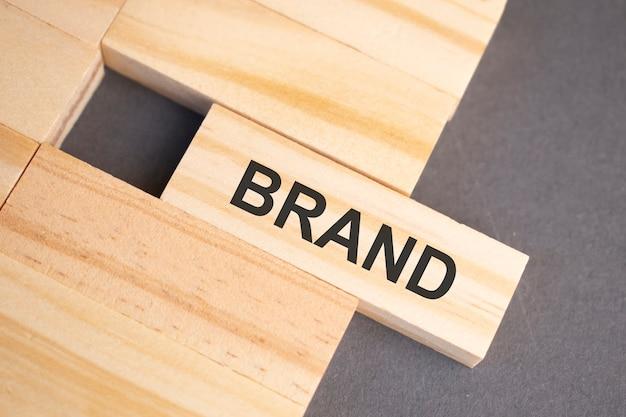 Słowa marki na drewnianych klockach na żółtym tle. koncepcja etyki biznesu.
