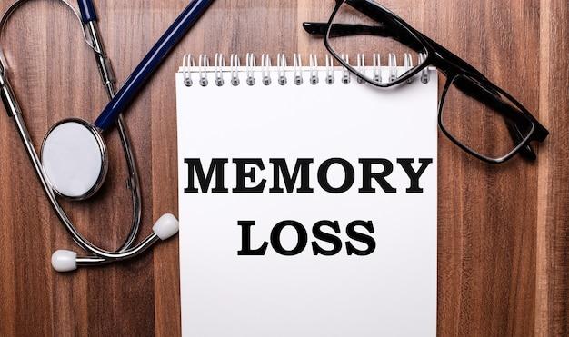 Słowa memory loss są zapisane na białym papierze na drewnianej powierzchni w pobliżu stetoskopu i okularów w czarnych oprawkach. pojęcie medyczne