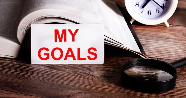 Słowa moje cele zapisane na białej karcie obok otwartej książki, budzika i lupy