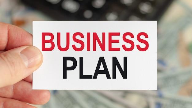 Słowa motywacyjne: biznesplan. mężczyzna trzyma kartkę z napisem: biznesplan. koncepcja biznesu i finansów