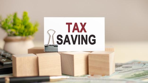 Słowa motywacyjne: oszczędność podatku. kartka z napisem tax saving. koncepcja biznesu i finansów.