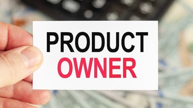 Słowa motywacyjne: właściciel produktu. mężczyzna trzyma kartkę z napisem: właściciel produktu. koncepcja biznesu i finansów