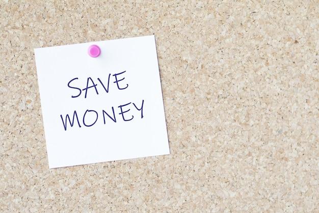"""Słowa """"oszczędzaj pieniądze"""" na papierze przyczepionym do tablicy szpilką"""