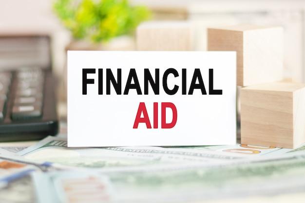 Słowa pomoc finansowa są zapisane na białej karcie papieru obok drewnianych kostek, banknotów, czarnego kalkulatora i zielonej rośliny