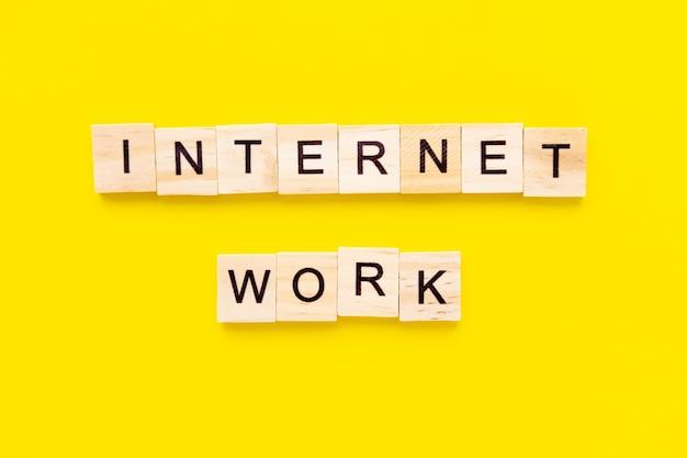 Słowa praca w internecie. drewniane klocki z napisem na żółtym stole. koncepcja zarządzania zasobami ludzkimi oraz rekrutacji i zatrudniania