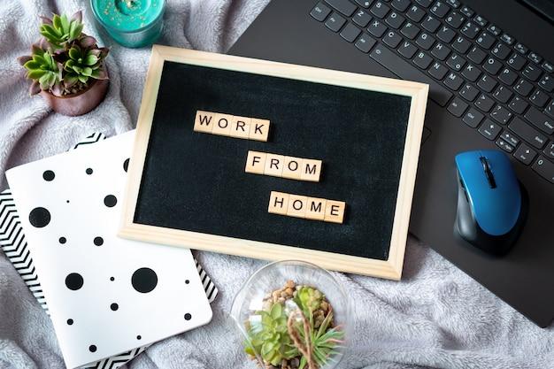 Słowa pracują z domu wykonanego z drewnianych klocków, koncepcja samo kwarantanny w domu jako środek zapobiegawczy przed epidemią wirusa. leżał płasko, laptop, notesy, pozostanie w domu w nagłych wypadkach