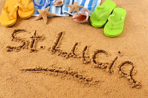 Słowa st lucia napisane na piaszczystej plaży, z maską do nurkowania, ręcznikiem plażowym, rozgwiazdą i klapkami