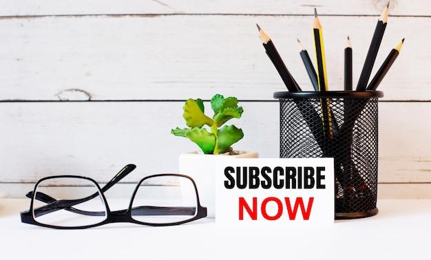 Słowa subscribe now zapisane na białej wizytówce obok ołówków na stojaku i okularów