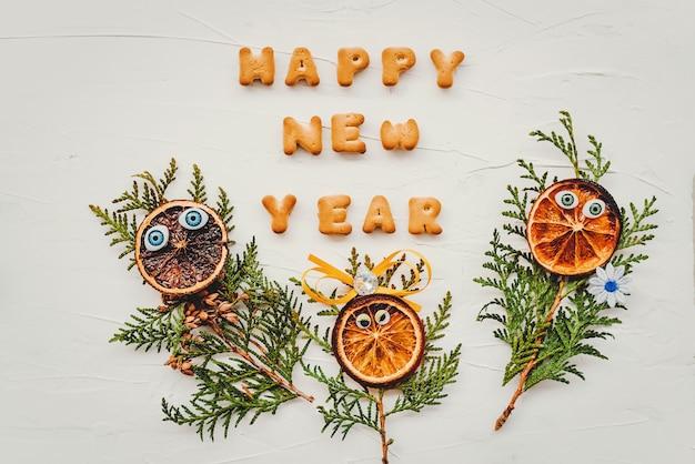 Słowa szczęśliwego nowego roku zostały napisane z liter ciasteczek. kompozycja płasko świeckich dla karty z pozdrowieniami.