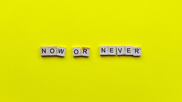 """Słowa """"teraz albo nigdy"""" na żółtym papierze. motywujący baner internetowy."""