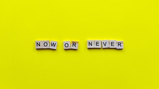 """Słowa """"teraz albo nigdy"""" na żółtym tle papieru."""
