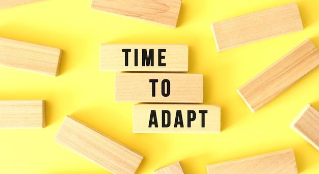 Słowa time to adapt są napisane na rozrzuconych drewnianych klockach na żółtym tle.