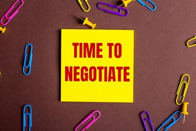 Słowa timr to negotiate są napisane na czerwono na żółtej naklejce na brązowej powierzchni obok wielokolorowych spinaczy do papieru