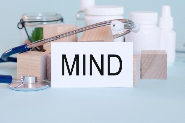 Słowa umysłu zapisane na białej karcie medycznej, ze stetoskopem, zielonym kwiatem, pigułkami lekarskimi i drewnianymi klockami na niebieskim tle.