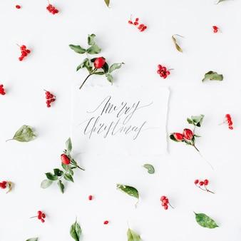 Słowa wesołych świąt i minimalny kreatywny wzór aranżacji jagód na białym tle.