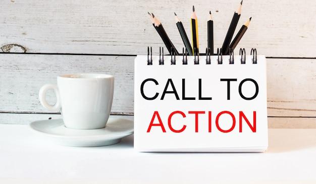 Słowa wezwanie do działania są zapisane w białym notatniku obok białej filiżanki kawy na jasnym tle