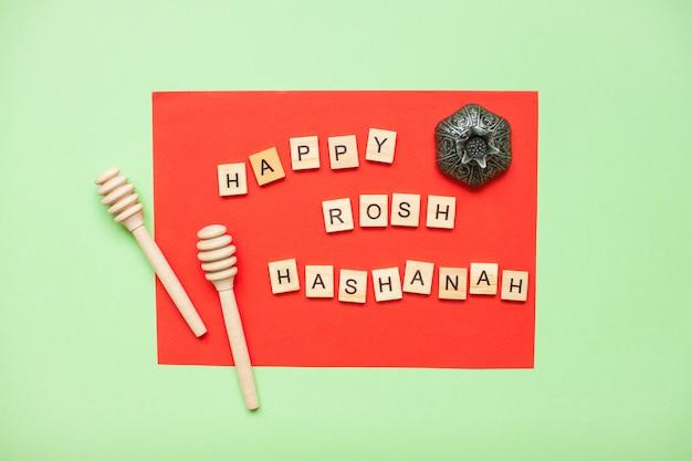 """Słowa z drewnianych klocków """"happy rosh hashanah"""" i drewniane łyżki do miodu na czerwono i zielono"""