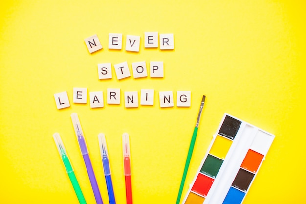 """Słowa z drewnianych klocków """"nigdy nie przestawaj się uczyć"""" i artykuły papiernicze na jasnożółtym tle"""