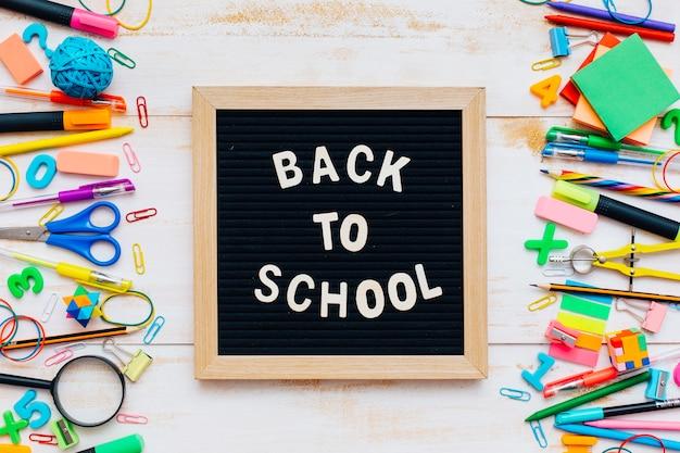 Słowa z powrotem do szkoły napisane kredą na szkolnym biurku z przyborów szkolnych z bliska