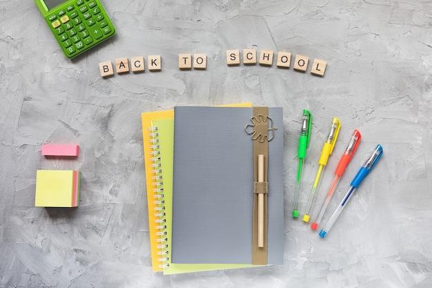 Słowa z powrotem do zeszytu szkolnego i długopisy na szarym tle