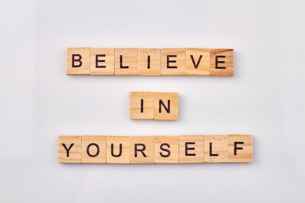 Słowa zapewniające pewność siebie i pewność siebie. wierzyć w siebie. drewniane kostki z literami robią słowa na białym tle.