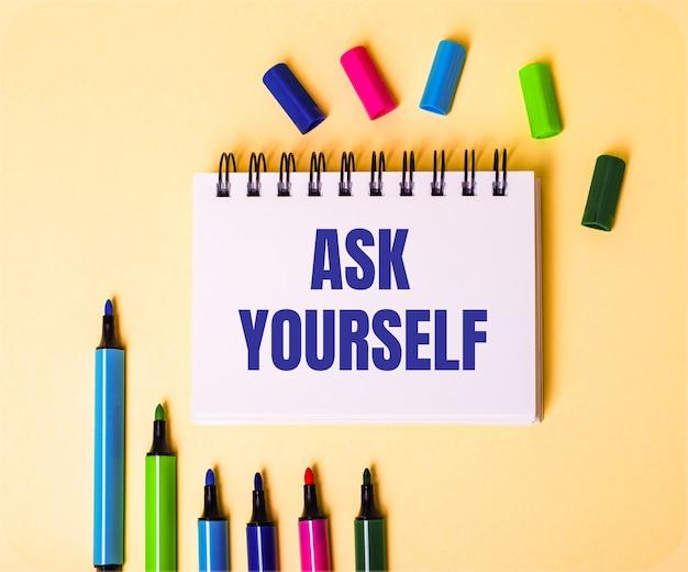 Słowa zapytaj siebie zapisane w białym zeszycie na beżowej powierzchni w pobliżu wielokolorowych markerów