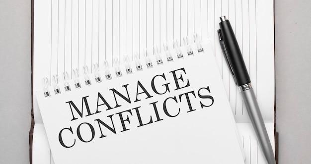 Słowa zarządzaj konfliktami tekst na notatniku i długopisie