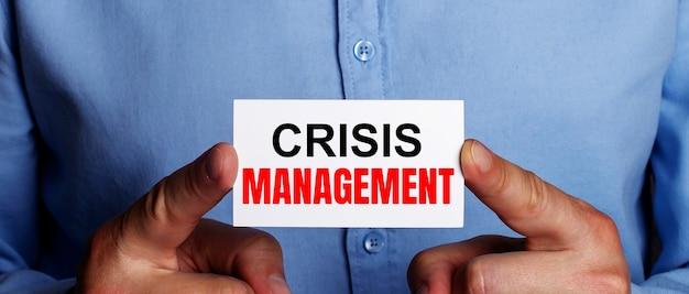 Słowa zarządzanie kryzysami są zapisane na białej wizytówce w dłoniach mężczyzny