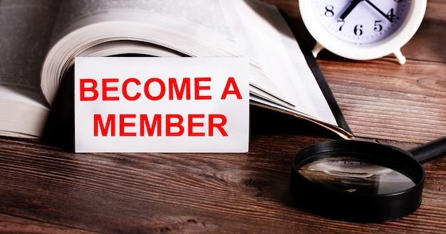 Słowa zostań członkiem zapisane na białej karcie obok otwartej książki, budzika i lupy