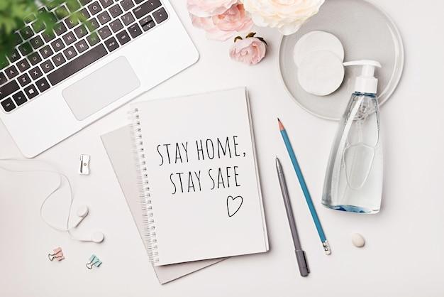 Słowa zostań w domu, zachowaj bezpieczeństwo są zapisane w notatniku, koncepcja samo kwarantanny w domu jako środek zapobiegawczy przed epidemią wirusa
