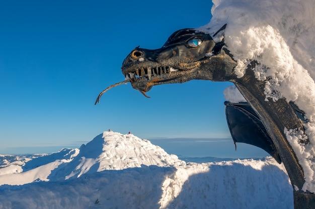 Słowacja. ośrodek narciarski jasna w słoneczny dzień. rzeźba smoka i dużo śniegu na szczycie chopoka. w tle ośnieżone szczyty górskie