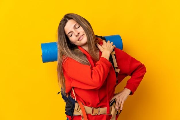 Słowacka alpinistka z dużym plecakiem na żółtej ścianie cierpiąca na ból barku z powodu wysiłku