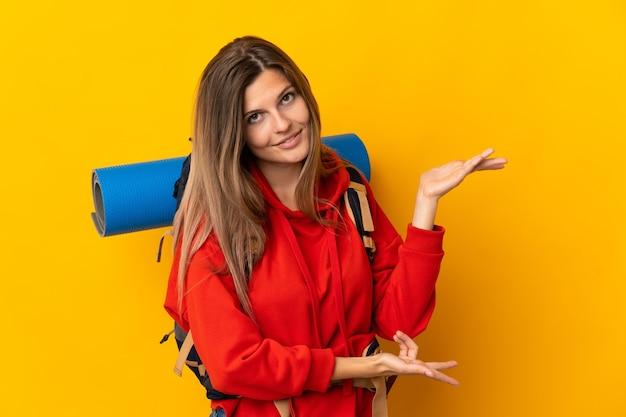 Słowacka alpinistka z dużym plecakiem na żółtej ścianie wyciągając ręce na bok, by zaprosić do siebie