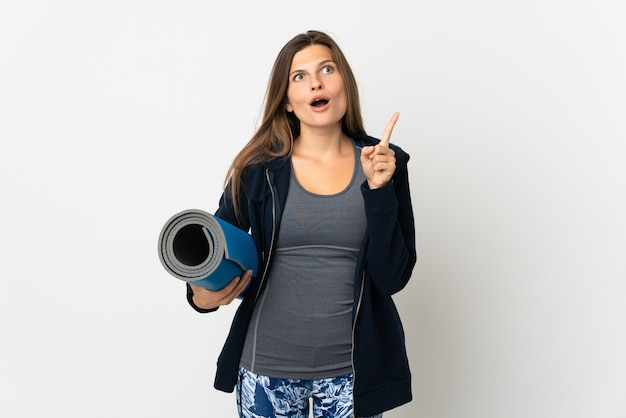 Słowacka dziewczyna idzie na zajęcia jogi na białym tle, myśląc o pomyśle wskazującym palec w górę