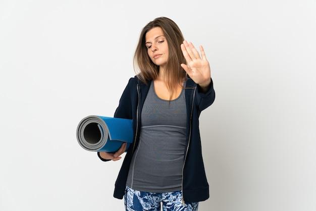 Słowacka dziewczyna idzie na zajęcia jogi na białym tle na białej ścianie, robi gest stop i rozczarowana