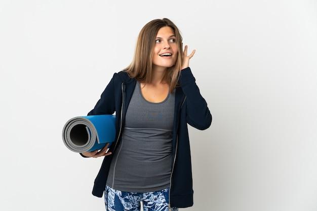 Słowacka dziewczyna idzie na zajęcia jogi na białym tle na białej ścianie, słuchając czegoś, kładąc rękę na uchu
