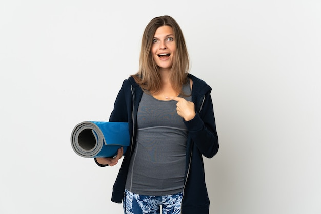 Słowacka dziewczyna idzie na zajęcia jogi na białym tle na białej ścianie z wyrazem twarzy zaskoczenia