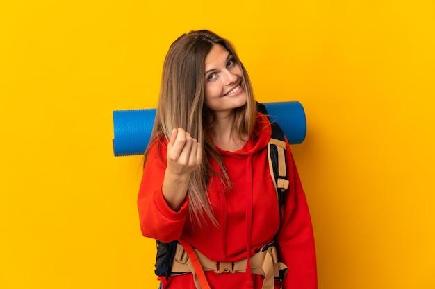 Słowacka góralka z dużym plecakiem na żółtym tle robiąca gest pieniędzy