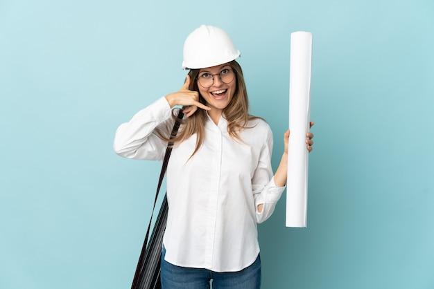 Słowacki architekt dziewczyna trzyma plany na białym tle na niebieskiej ścianie, dzięki czemu telefon gest. oddzwoń do mnie znak