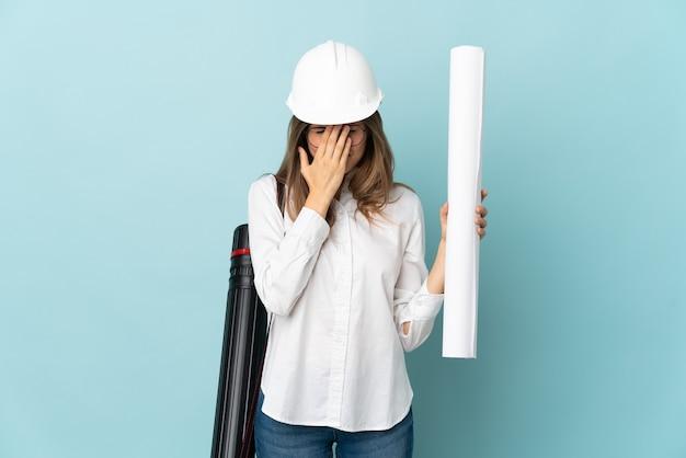 Słowacki architekt dziewczyna trzyma plany na białym tle na niebieskiej ścianie z wypowiedzi zmęczony i chory