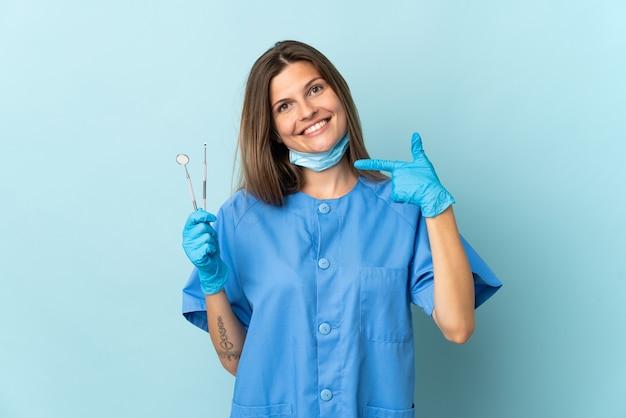 Słowacki dentysta trzymając narzędzia samodzielnie na niebieskiej ścianie, dając kciuk do góry gestu