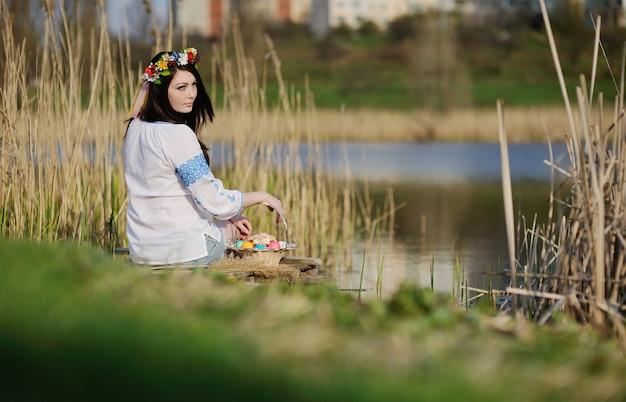 Słowiańska dziewczyna w ukraińskiej koszuli siedzi na moście z wielkanocą