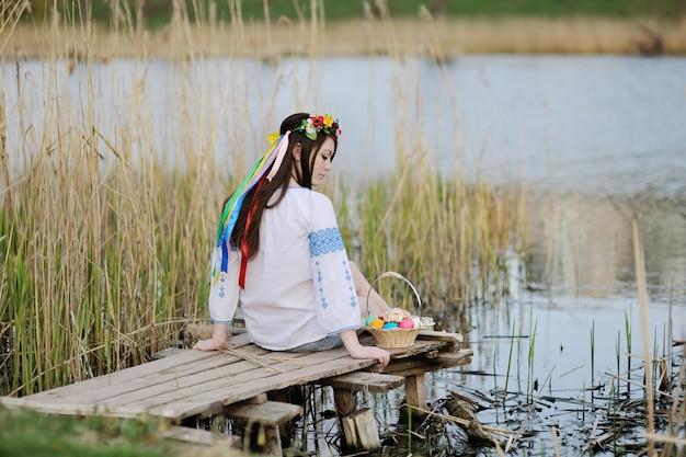 Słowiańska dziewczyna w ukraińskiej koszuli siedzi na moście z wielkanocy