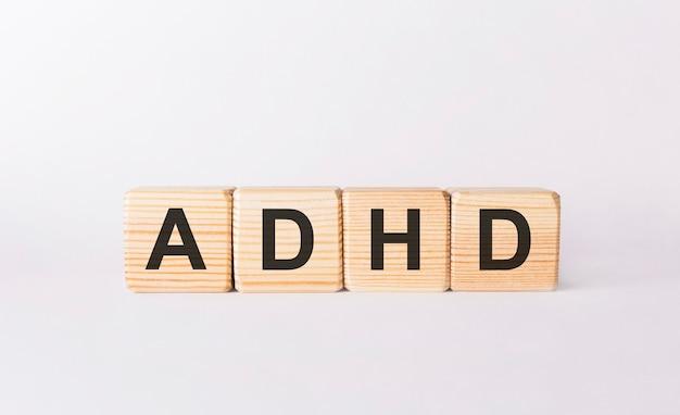 Słowo adhd wykonane z drewnianych klocków na białym tle