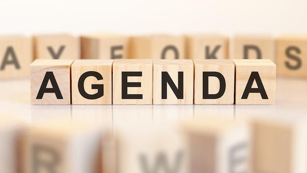 Słowo agenda jest zapisane na drewnianej konstrukcji z kostek. koncepcja biznesowa i finansowa.