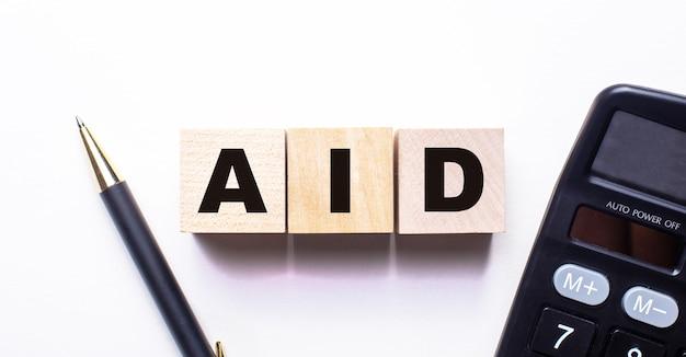 Słowo aid jest zapisane na drewnianych kostkach między długopisem a kalkulatorem na jasnej powierzchni.