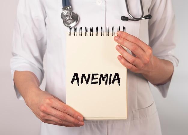 Słowo anemii na papierze zeszytowym w ręku lekarza