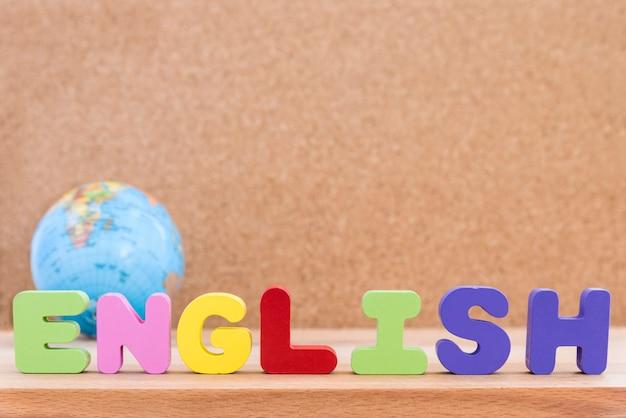 Słowo angielski z globu na tle drewniane