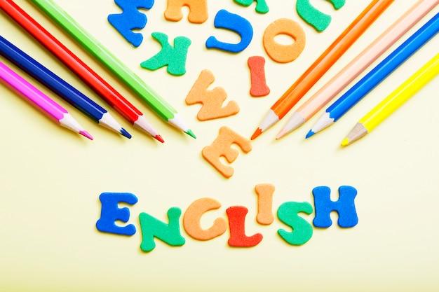 Słowo angielskie wykonane z kolorowych liter z kolorowymi ołówkami. nauka nowej koncepcji językowej